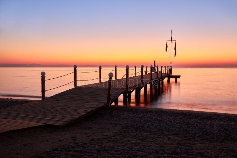 Kalm warme zee en grote houten pier met een zwemgebied bij zonsopgang stock foto's