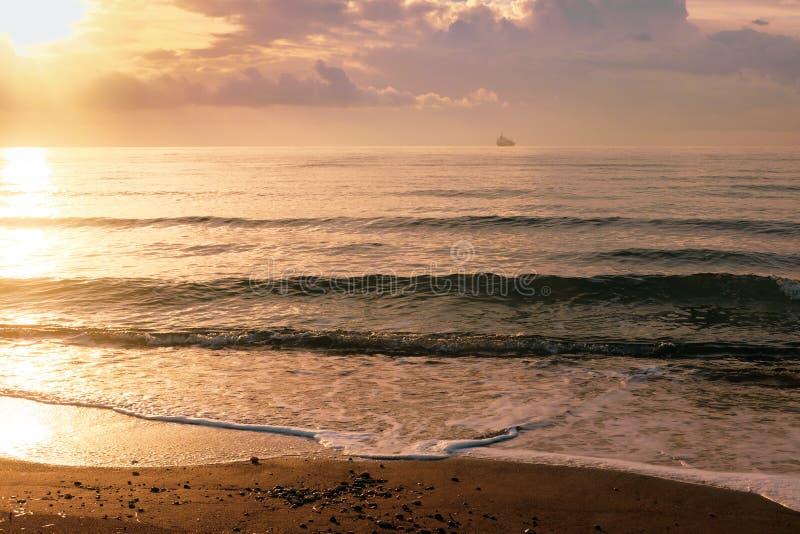 Kalm-zeegolven in gouden licht in Larnaca stock afbeeldingen