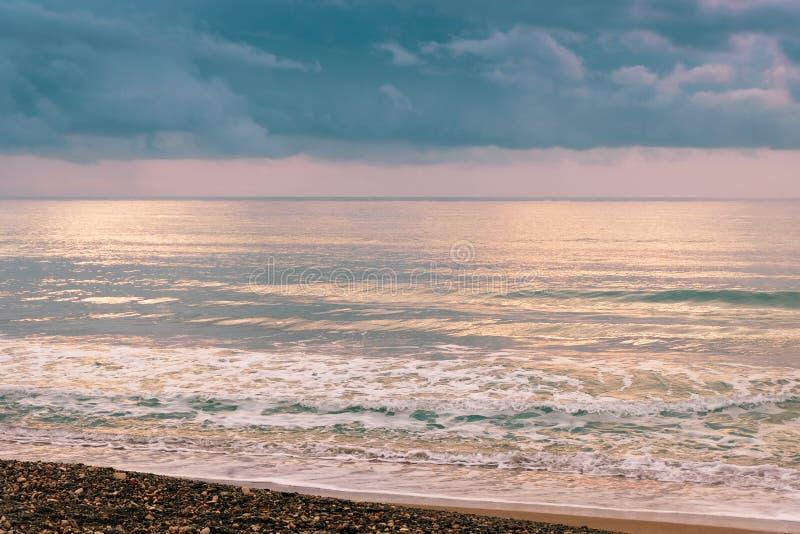 Kalm zeegolven tegen een donkere en stormachtige lucht stock foto