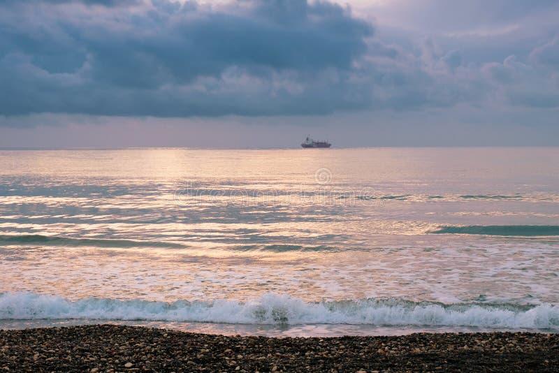Kalm zeegolven tegen een donkere en stormachtige lucht royalty-vrije stock foto