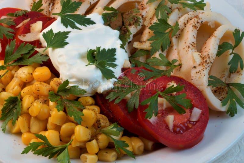 Kalmar mit Tomaten, Mais, Knoblauch, Sauerrahm und Kräutern stockbilder