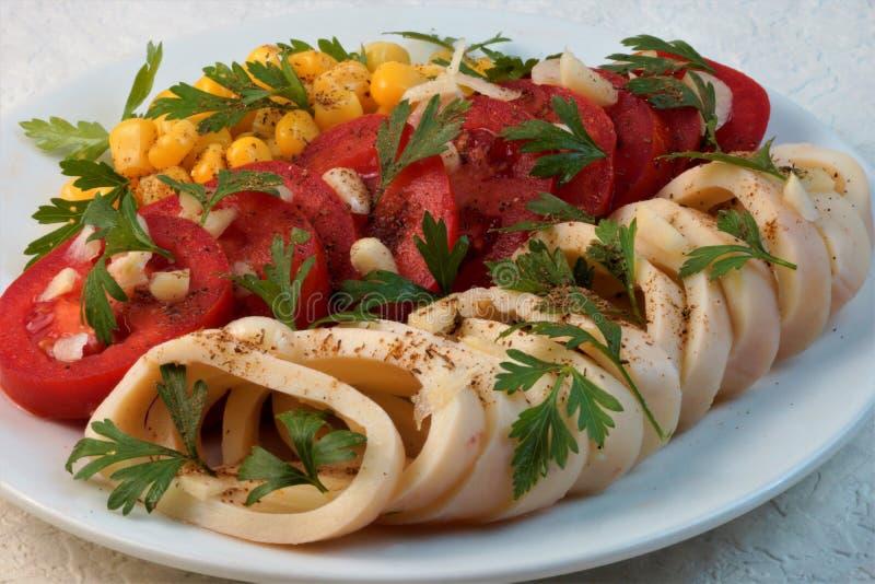Kalmar mit Tomaten, Mais, Knoblauch und Kräutern stockbild