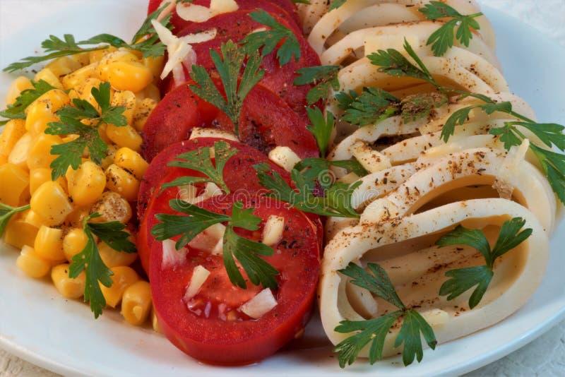 Kalmar mit Tomaten, Mais, Knoblauch und Kräutern lizenzfreie stockbilder