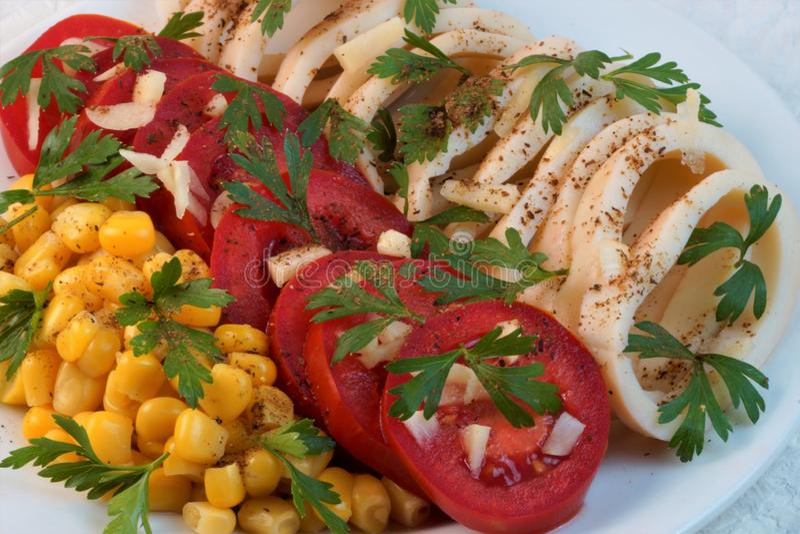 Kalmar mit Tomaten, Mais, Knoblauch und Kräutern stockfoto