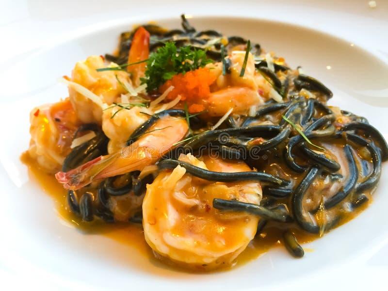 Kalmar-Tintenspaghettis mit würziger Garnele Suppe oder Tom Yum Kung, der auf die weiße Platte gesetzt wurde Dieses ist eine Fusi lizenzfreie stockfotos