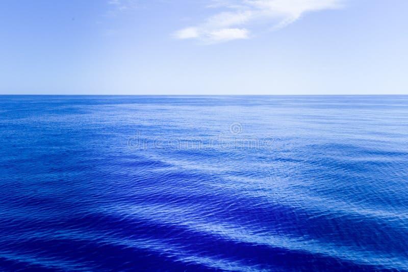 Kalme blauwe overzeese oppervlakte met weerspiegeling van licht stock afbeeldingen