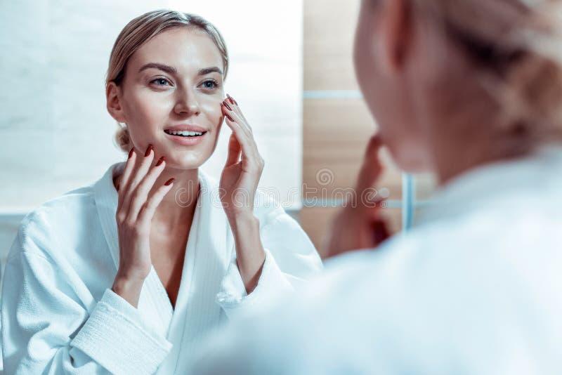 Kalme blondevrouw wat betreft haar gezicht en het controleren van staat van de huid royalty-vrije stock foto