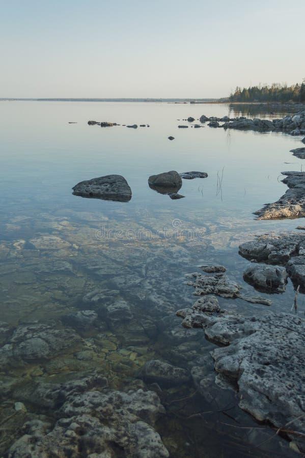 Kalme duidelijke oever van Meer Huron met kalksteenrotsen stock foto