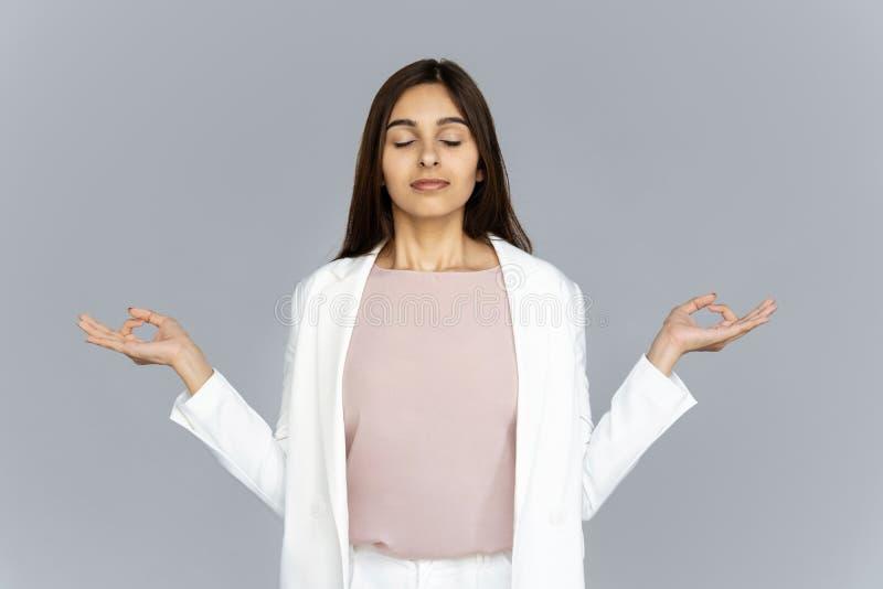 Kalme gezonde Indische bedrijfsvrouw die op grijze studioachtergrond mediteren royalty-vrije stock foto