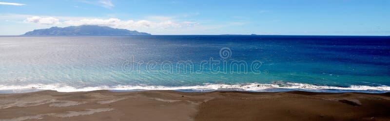 Kalme golven, blauwe wateren, zwart zandstrand royalty-vrije stock fotografie