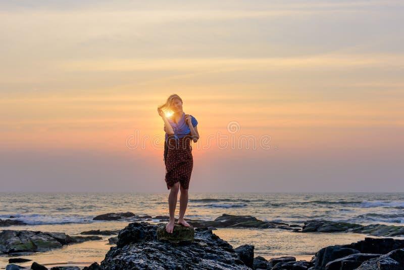 Kalme jonge vrouw die zich op de achtergrond van het overzees bevinden en vreugde uitdrukken Het vrouwelijke stellen tegen pracht stock afbeelding