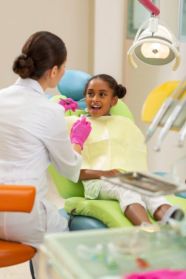 Kalme jonge vrouwelijke geduldige zitting bij de tandartsen royalty-vrije stock fotografie