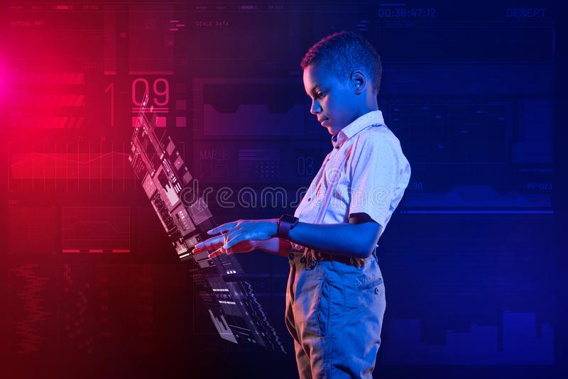 Kalme jongen die geconcentreerd terwijl het creëren van een hologram kijken stock afbeeldingen