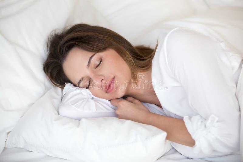 Kalme mooie vrouwenslaap vreedzaam op witte bladen in bed royalty-vrije stock foto's