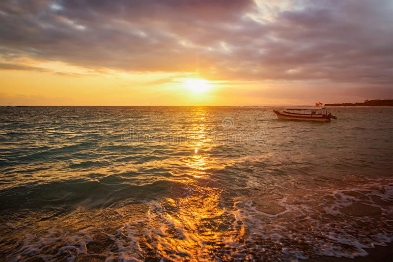 Kalme oceaan met boot op zonsopgang stock fotografie