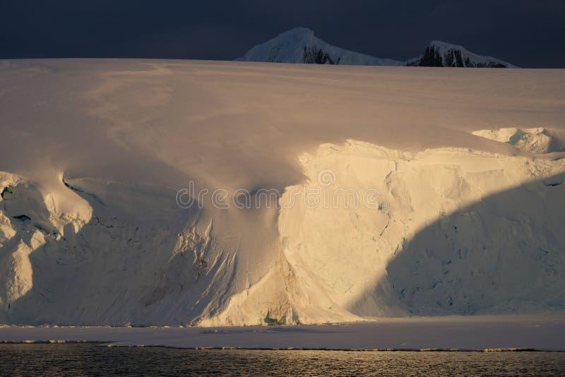Kalme oranje de middernachtzonsondergang van Antarctica op gletsjer stock foto's