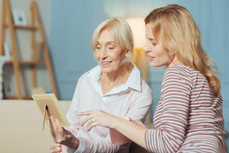 Kalme oude een oude foto tonen en vrouw die nadenkend kijken stock afbeeldingen