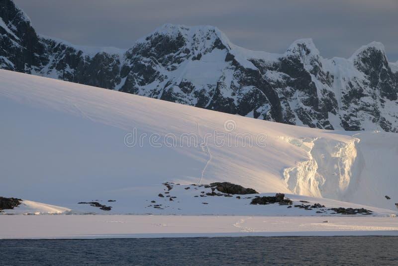 Kalme roze de middernachtzonsondergang van Antarctica over gletsjers stock foto