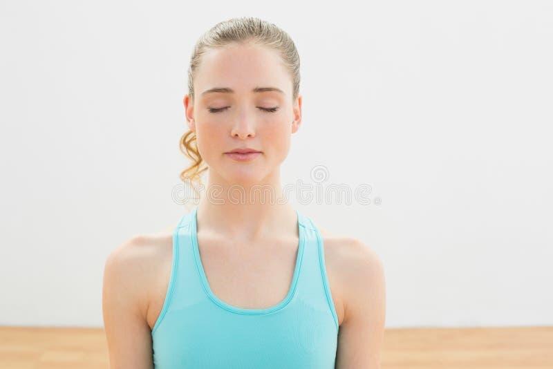 Kalme slanke blondezitting op vloer met gesloten ogen royalty-vrije stock afbeeldingen
