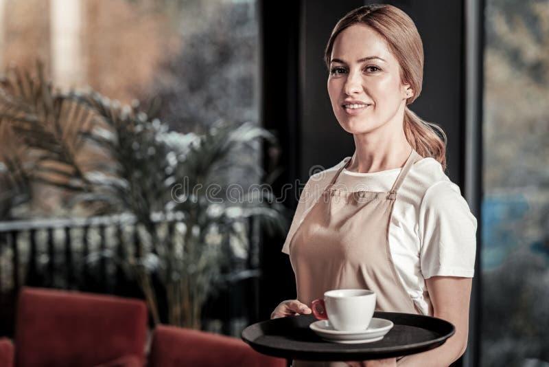 Kalme vriendschappelijke serveerster die zich met een kop van koffie op haar dienblad bevinden stock afbeeldingen
