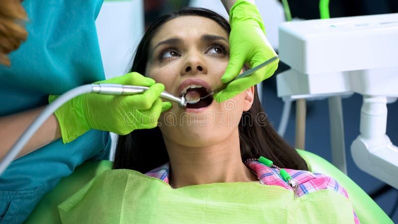 Kalme vrouwenzitting als voorzitter terwijl tandarts die tandboor gebruiken om tanden te behandelen stock afbeelding
