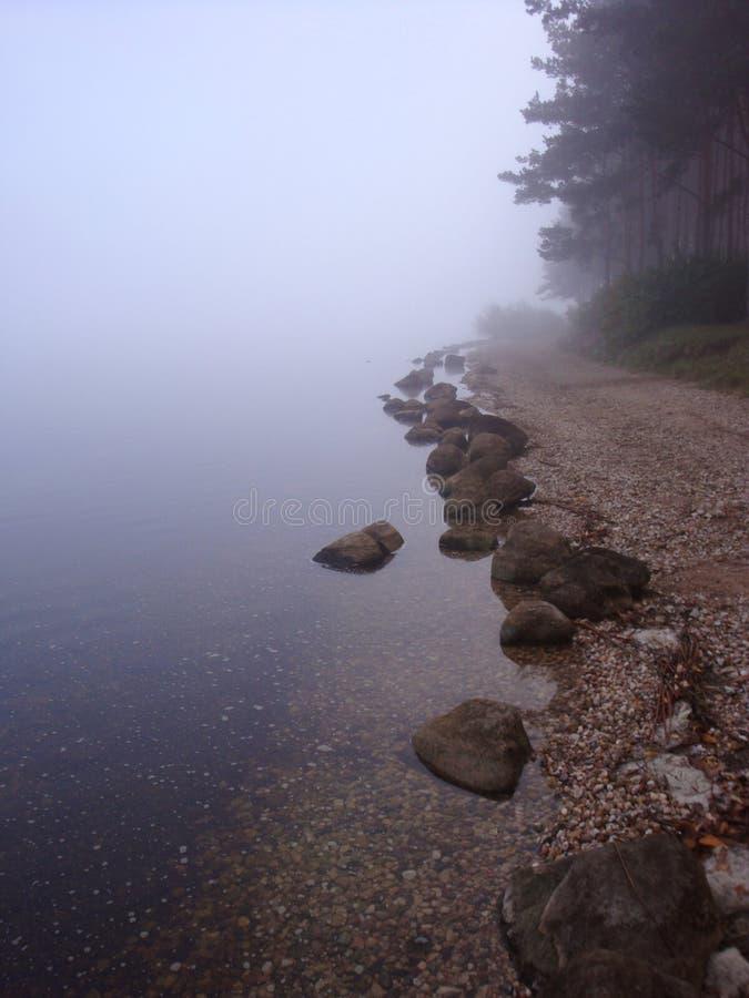 Kalme water witte en blauwe tonen die over vlotte rotsen bij de meerkust stromen stock foto