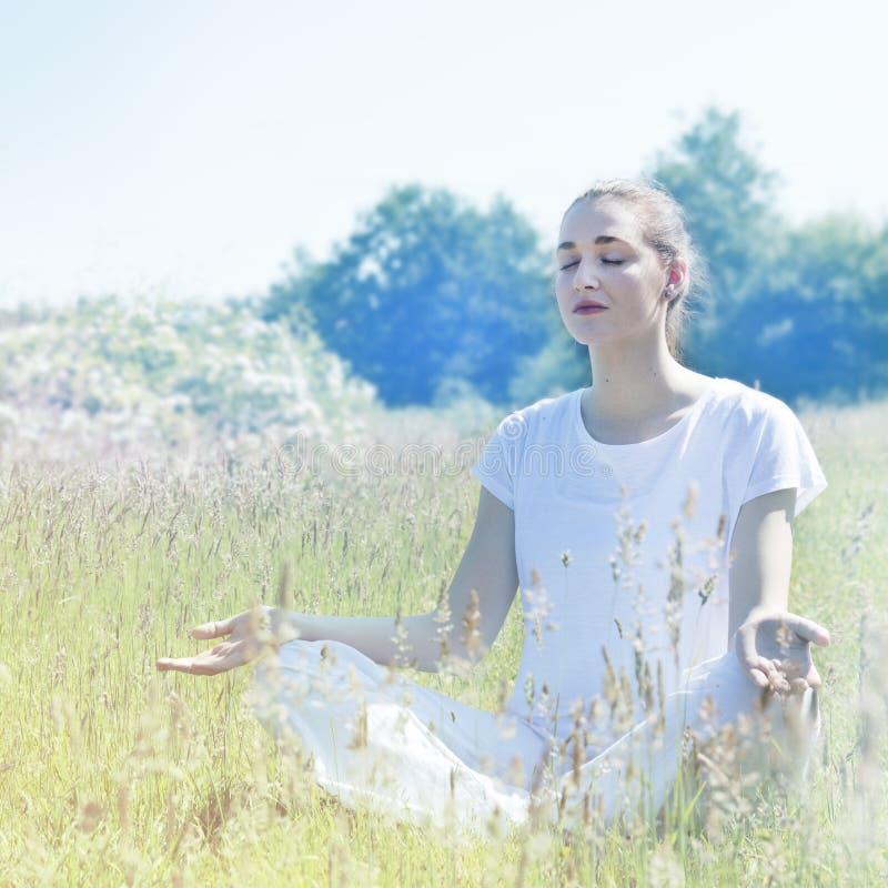 Kalme yogavrouw die zacht wit in verbinding dragen aan aard royalty-vrije stock afbeelding