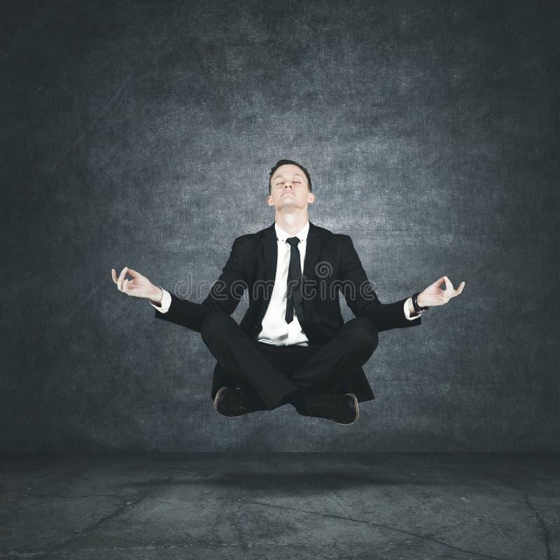 Kalme zakenman die tijdens meditatie levitatie ondergaan stock foto