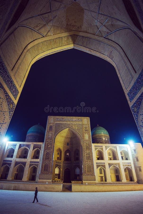 Kalon清真寺,Mir我阿拉伯人Madrasah广场,历史的古老修造的废墟在晚上,布哈拉,乌兹别克斯坦 库存图片