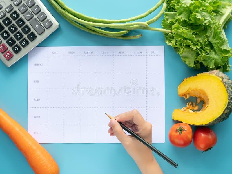 Kalorie kontrolują, posiłku plan, karmowa dieta i ciężar straty pojęcie, odgórny widok ręka podsadzkowego posiłku plan na pustym  zdjęcia royalty free