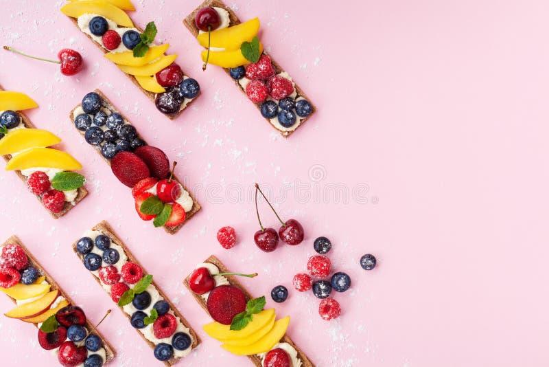 Kalorienarmer Imbiss oder Nachtisch von den Sandwichen mit sahnigem Käse- und SommerBeerenobst auf Draufsicht des rosa modischen  lizenzfreies stockfoto