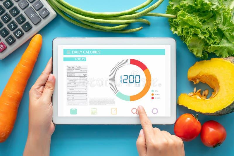 Kalorier som räknar, bantar, matkontroll och begreppet för viktförlust kvinna som använder kaloriräknareapplikation på minnestavl arkivbild