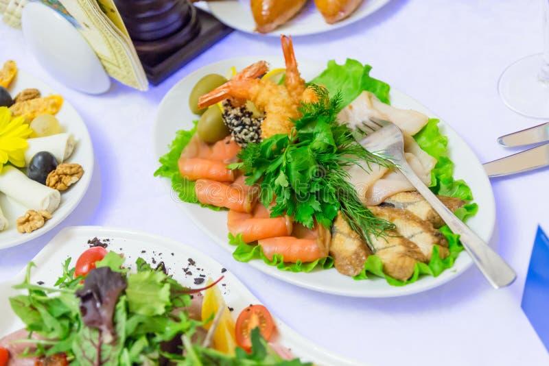 Kalte Aperitifs, Meeresfrüchte und grünes Gemüse am Bankettisch im Restaurant stockfotografie
