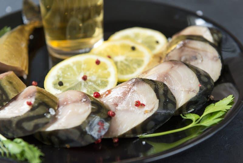 Kalte geräucherte Makrele mit Gewürzen auf einer Platte, Zitronenstücke, gesalzene Fische, Bierimbiß lizenzfreies stockfoto