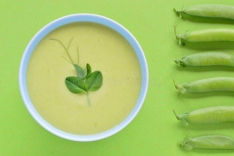 Kalte sahnige Suppe und Erbsenhülse der grünen Erbse. stockfotografie
