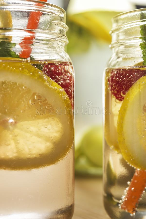 Kalte Sommererfrischungen im Glasgefäß mit Zitrone stockfotografie