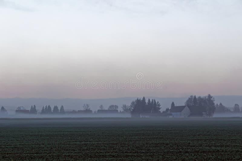 Kalte und nebelige Landschaft des Bauerndorfes stockfoto