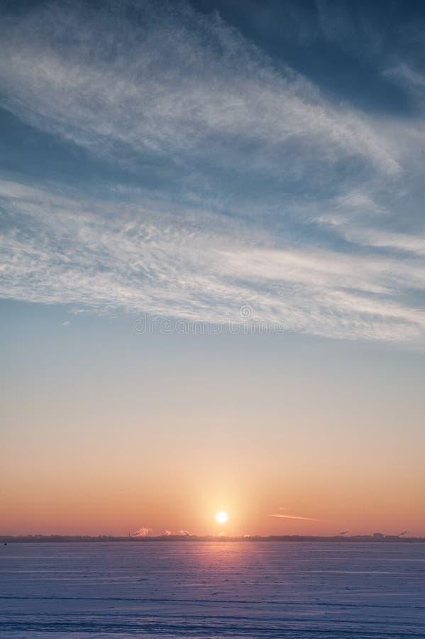 Kalte Winterlandschaft mit Schnee, Himmel und Sonne auf dem Horizont stockbild