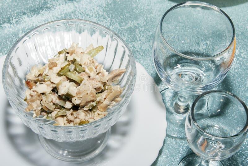 Kalter Aperitif des Gemüses und der Pilze Frischer Salat in der Schüssel und in den leeren Weingläsern auf Tabelle stockfoto