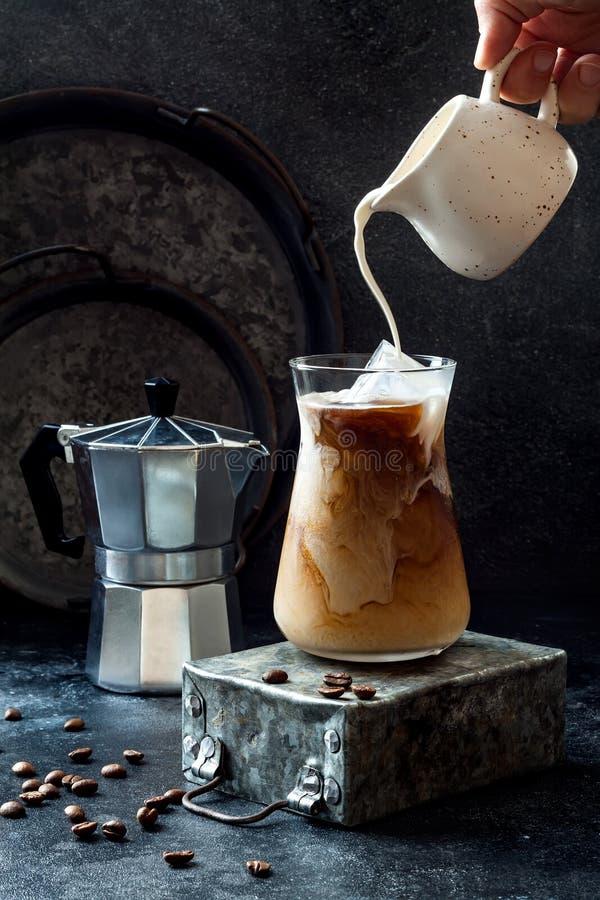 Kalter Auffrischungsgefrorener Kaffee in einem hohen Glas und in den Kaffeebohnen auf dunklem Hintergrund Auslaufende Creme in Gl lizenzfreie stockbilder