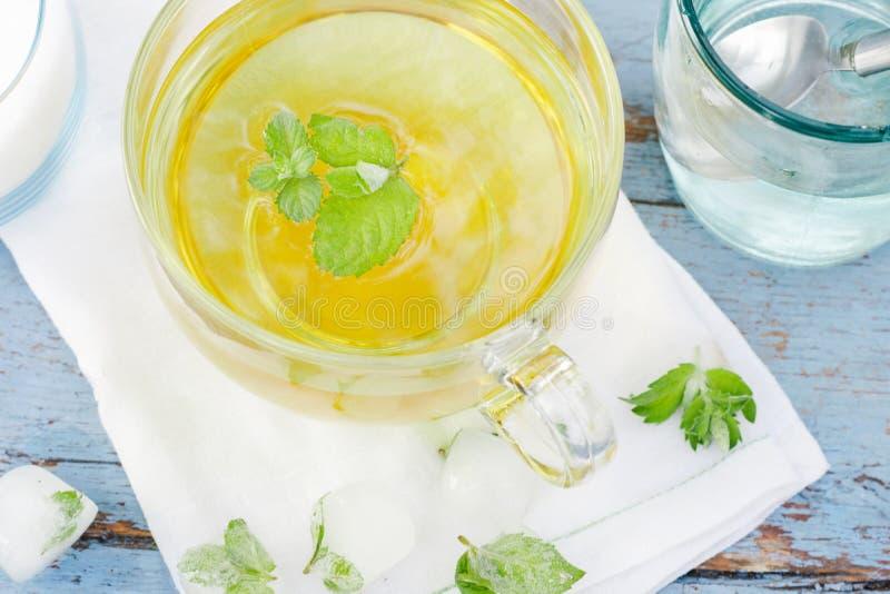 Kalter frischer tadelloser Blatttee, tadelloser Tee mit Eiswürfeln in einer Glasschale auf einem Holztisch lizenzfreie stockbilder
