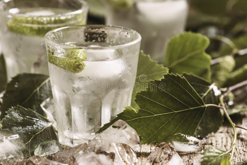Kalter russischer Wodka auf Birkenknospen, zerquetschtes Eis, Birkenblätter, Weinleseholztisch stockbilder