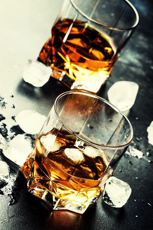 Kalter Whisky mit Eiswürfeln in der schwarzen Tabelle, selektiver Fokus lizenzfreie stockbilder