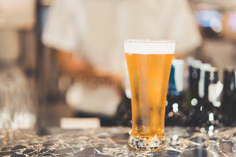 Kaltes Bier auf dunkler Marmorgegenbar, unscharfer Barmixer als Hintergrund stockfoto