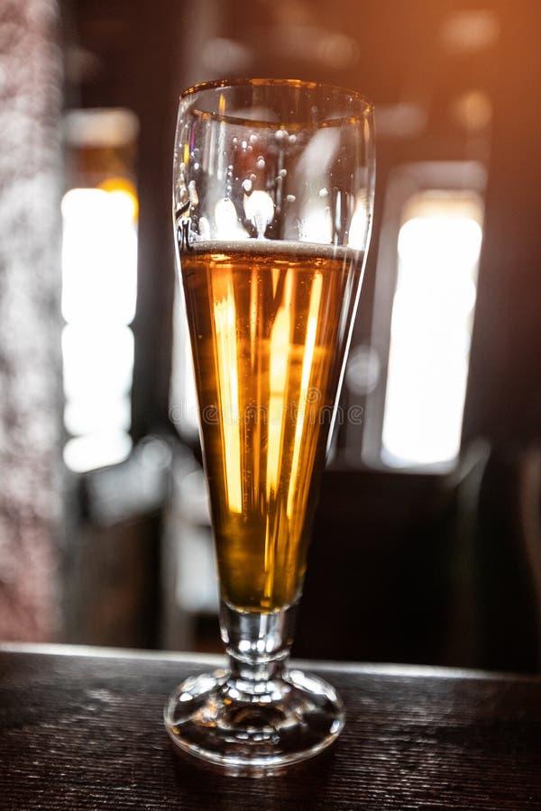 Kaltes Bier in einem Glas auf einem Holztisch in der Kneipe stockfoto