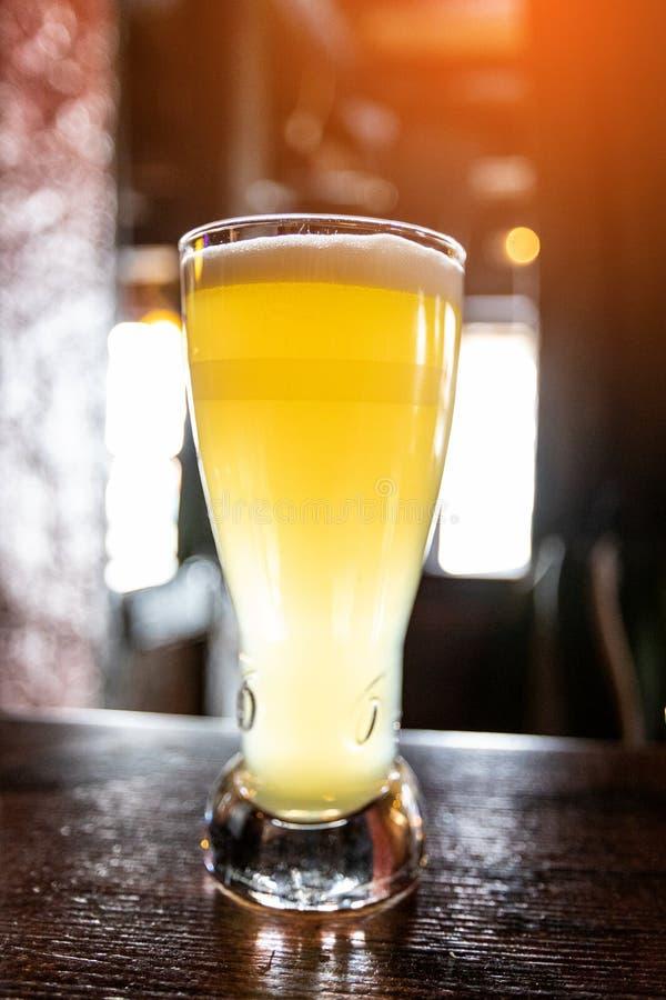 Kaltes Bier in einem Glas auf einem Holztisch in der Kneipe lizenzfreies stockfoto