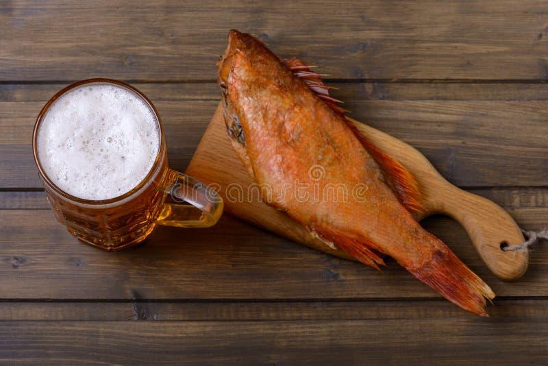 Kaltes Bier und geräucherte Fische auf Tabelle lizenzfreie stockbilder