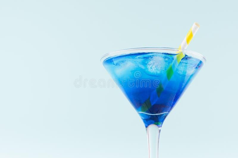 Kaltes blaues Lagunengetränk des Sommers mit Eiswürfel, gelbes gestreiftes Stroh in elegantem Martini-Glas auf tadellosem Pastell stockbilder