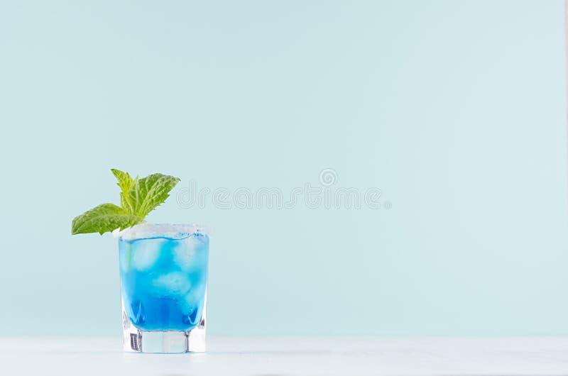 Kaltes blaues Lagunengetränk des Sommers mit Eiswürfeln, Salzkante, grüne Minze im eleganten Schnapsglas auf tadellosem Pastellhi stockfotografie