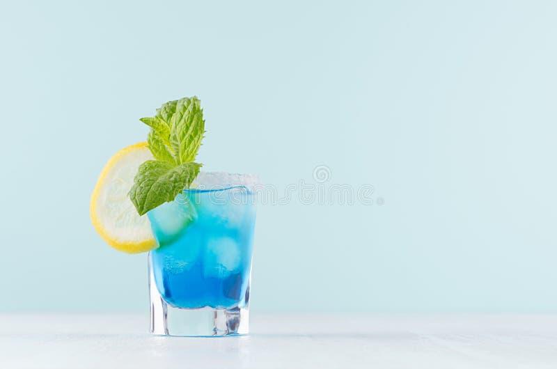Kaltes blaues Lagunengetränk des Sommers mit Eiswürfeln, Salzkante, grüne Minze, Zitronenscheibe im eleganten Schnapsglas auf tad stockbild